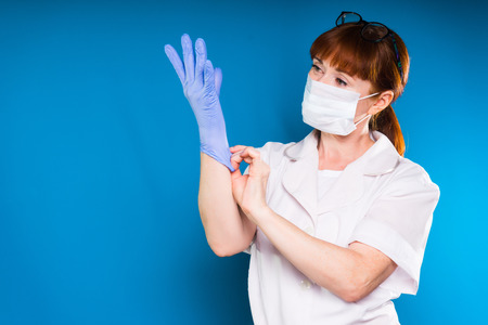 a woman in a medical white coat and wearing a mask puts on her gloves and looks at her hands, isolated on a blue background Фото со стока
