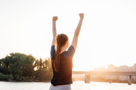 a girl in a tracksuit on a run on the river bank. Woman doing exercises and raising her hands up Stock Photo