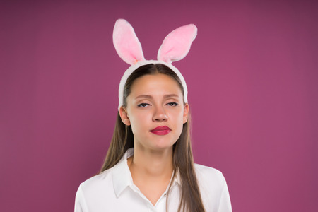 pretty girl with pink hare ears on her head looking displeased at the camera and chews Stock Photo