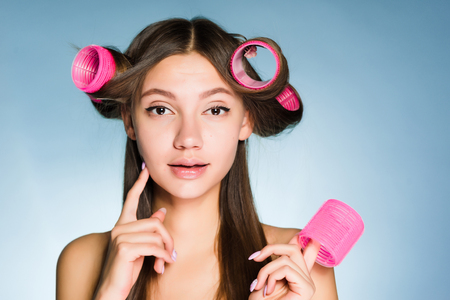 attractive young girl wants a beautiful hairstyle, on her head big pink hair curlers