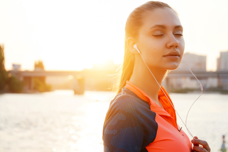 the girl in a sports suit against the background of the river closed her eyes and enjoys music in headphones at sunset