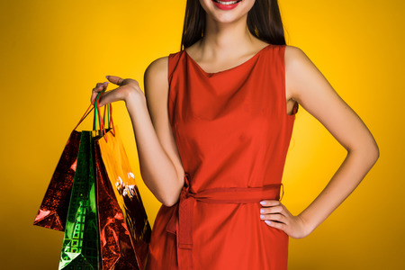 a girl in a fashionable red dress rejoices on a black Friday, bought many presents to friends and family