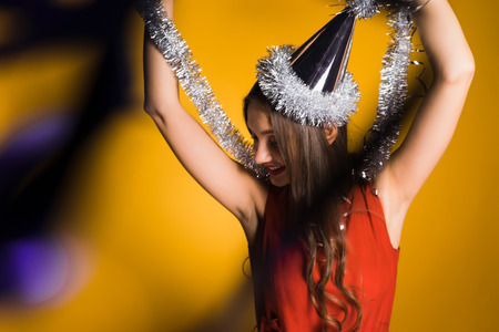 happy young girl celebrates the new year and christmas in a festive cap, holds a silver tinsel