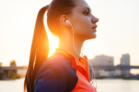 girl with headphones and comportant clothes jogging listening to music at sunset