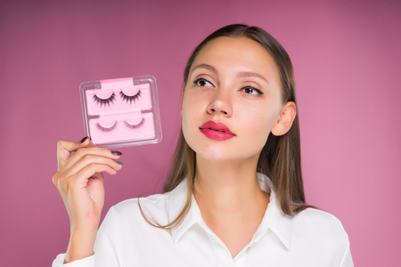 cute girl with big lips holding false eyelashes and looking away thoughtfully, isolated on pink background