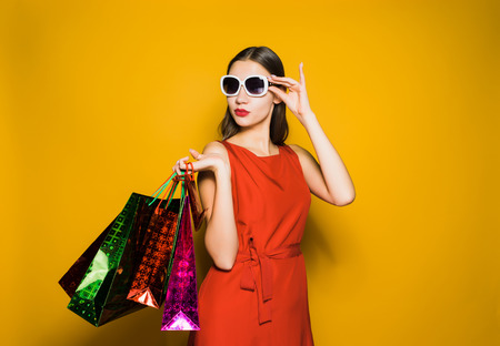 a young girl in sunglasses went shopping, on a black Friday, bought a lot of gifts