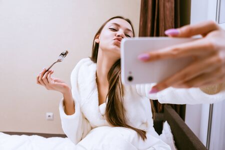 funny young girl is having breakfast in bed, recently woke up, makes selfie Stock Photo