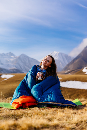 a smiling young girl holding a mug with hot tea, sitting in a sleeping bag against the background of the Caucasian mountains, loves to travel