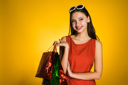happy young girl in a red dress bought presents for the new year, loves a black Friday