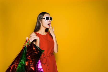 a surprised stylish young girl in sunglasses bought a lot of gifts for the new year on a black Friday