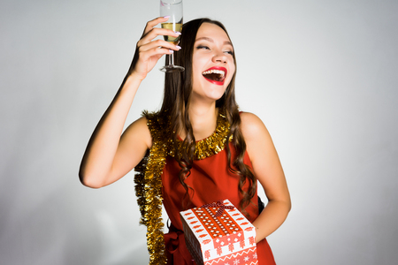 happy young girl celebrating the new year, received a gift, holds a glass of champagne