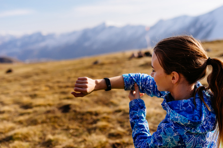 a young girl in a blue jacket travels along the Caucasian ridge, looks at the time on the wristwatch