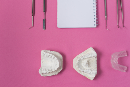 on the pink surface lie a plaster cast of teeth, a notebook and dental instruments