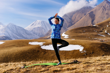 active young girl doing yoga in the background of the Caucasian mountains