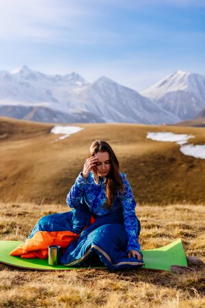 a young tourist girl travels along the Caucasian ridge, sits in a sleeping bag Archivio Fotografico