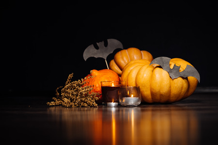 on a dark background lie yellow Halloween pumpkins, burning scented candles, a branch of dry grass