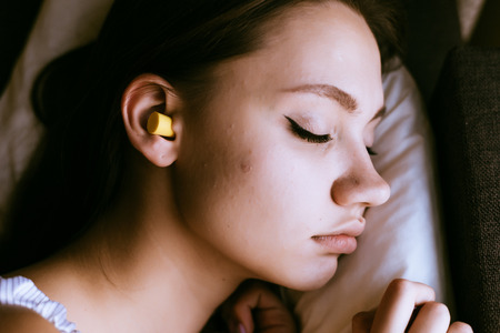 young girl sleeping in the bed, in the ears yellow earplugs against the noise Stock Photo