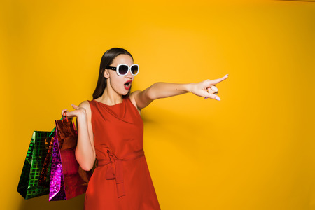 stylish girl in sunglasses went shopping with a surprised finger at something