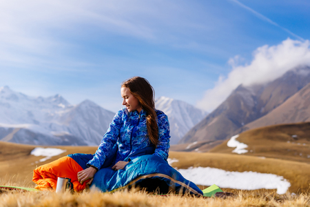 happy young girl in a blue jacket sits on the background of the Caucasian mountains, enjoys nature and warm weather Stock Photo - 91212632