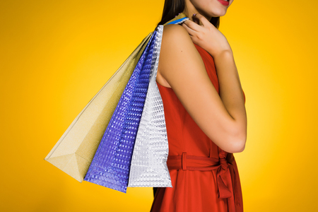 girl in red dress has bought many gifts for the new year, on a yellow background Stock Photo