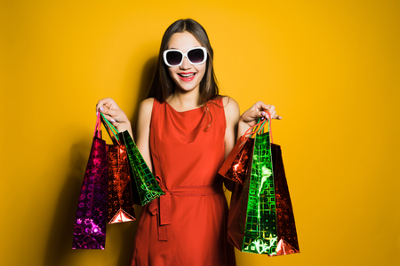 happy young girl in sunglasses went for gifts on a sale