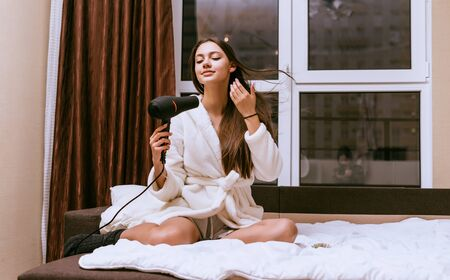attractive young girl sits on a bed dries her long hair with a hairdryer