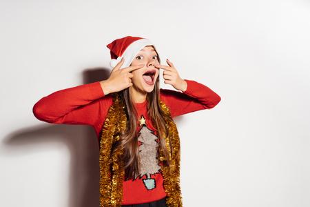 面白い若い女の子は、新年を待っているお祝いの服で、鼻に指で示しています 2018