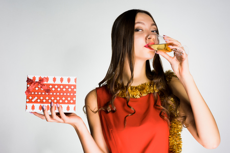 young beautiful girl in red dress celebrates the new year 2018, drinks champagne and holds a gift