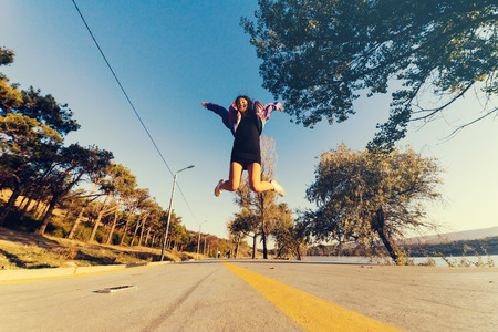 happy stylish girl jumps high, on the road