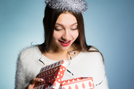 happy young girl received a gift for the new year, looks in the gift box Stock Photo