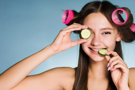 happy smiling girl wants to look good, on the head of curlers, keep pieces of cucumber for moisturizing the skin