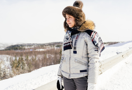 a young girl in warm clothes and a fur hat travels north, Iceland, around white snow