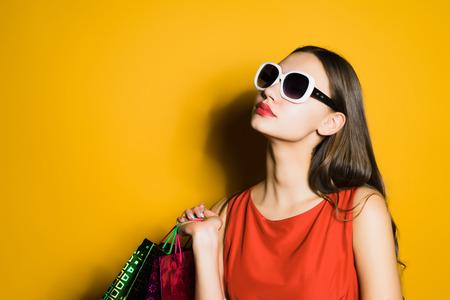 mooi jong meisje in zonnebril houdt van winkelen, kocht een heleboel dingen, in een zwarte stuiver Stockfoto