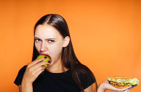 young sad girl sits on a diet, eats a healthy green apple, Holds a harmful burger Imagens