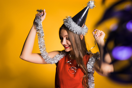 happy girl in a red dress holds a silver tinsel celebrates the new year 2018