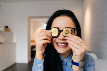 happy smart brunette with glasses holds golden bitcoins in hands and closes their eyes, smiles