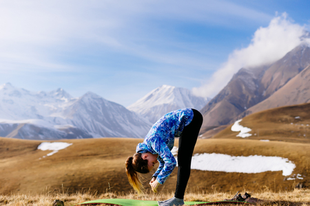 active young girl leads a healthy lifestyle, loves sports tourism, is engaged in yoga in the background of the Caucasian mountains