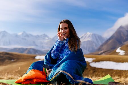 happy young girl travels through the Caucasian mountains, sits in a sleeping bag, enjoys nature