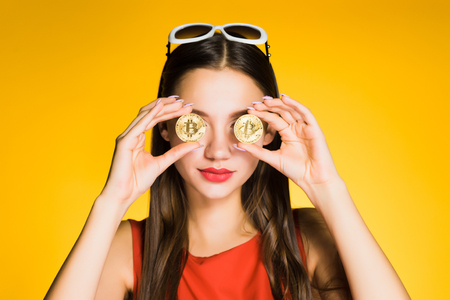 young beautiful girl holds golden bitcoins in hands and closes their eyes, on a yellow background Stock Photo