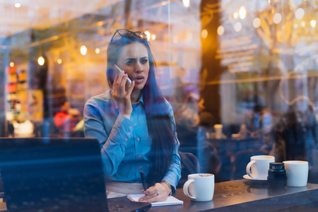 dissatisfied busy girl freelancer is negotiating by phone, in a cafe