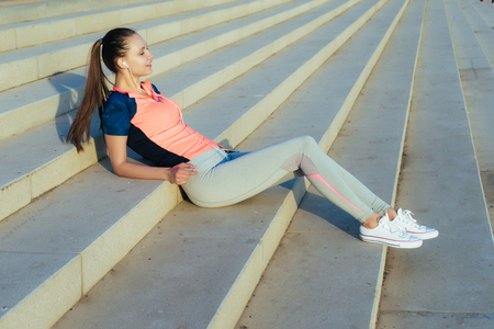 beautiful young girl resting after training on the steps, in the sun