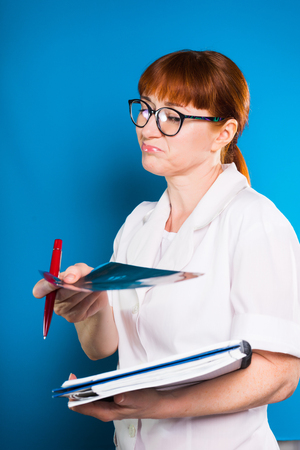 experienced redhead female doctor with glasses holds cards of patients in hands