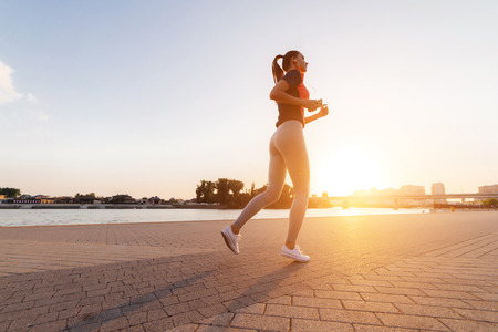 a sporty slender young girl runs along the river in the rays of the evening sun Stock Photo