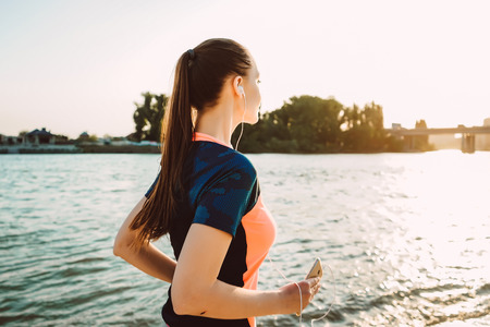 long-haired athletic girl leads a healthy lifestyle, runs along the river at sunset Zdjęcie Seryjne