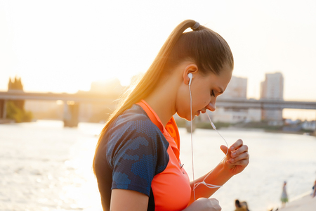 beautiful young girl in sportswear listening to music on headphones on the background of the river and sun