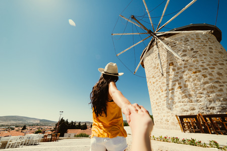 Woman holds boyfriend hand follow me,old windmills. Summer holidays in europe,vacation,traveler.Spain,greece,turkey.