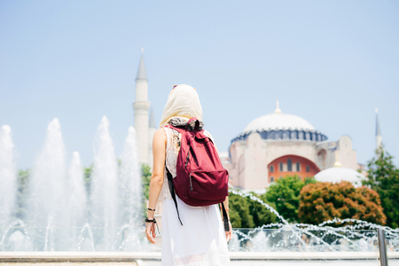 An unrecognizable woman in a scarf with a backpack on the background of a mosque and a fountain. Summer vacation, traveler Stock Photo
