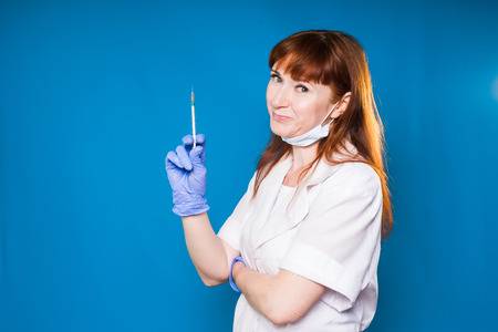 smiling experienced redheaded woman doctor in white medical dressing gown holds a syringe in hands