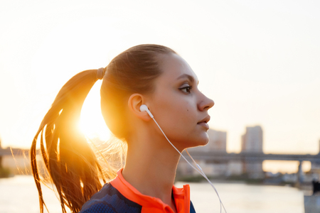 young purposeful girl runs by the river at sunset, listens to music on headphones