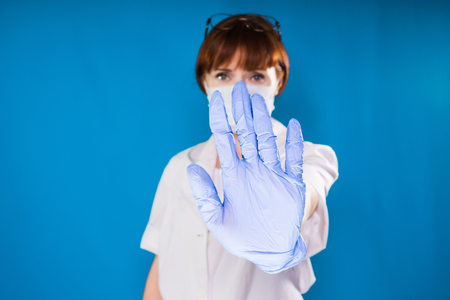 woman doctor in white medical dressing gown and blue silicone gloves showing palm